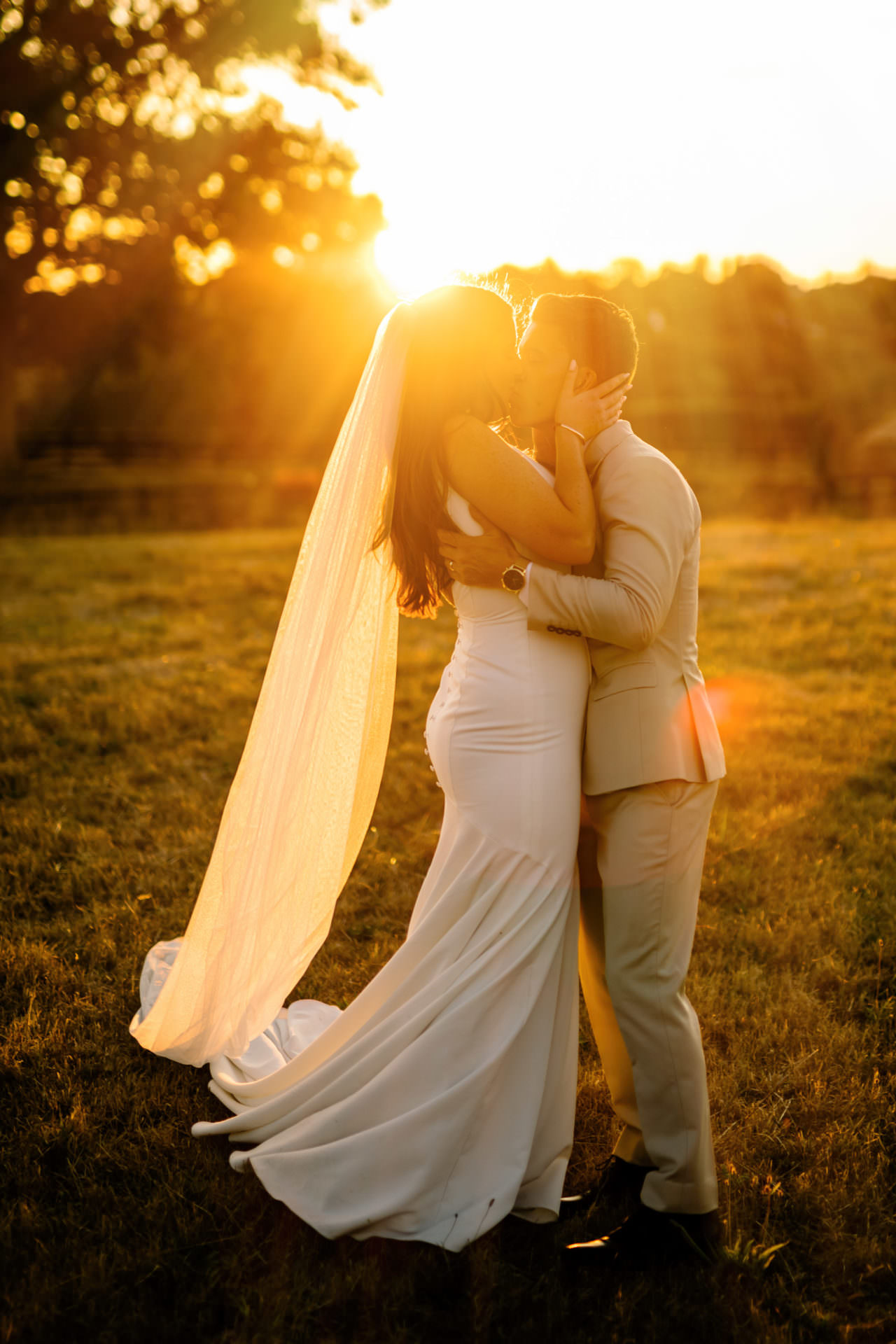 Golden hour wedding photo of bride and groom kissing