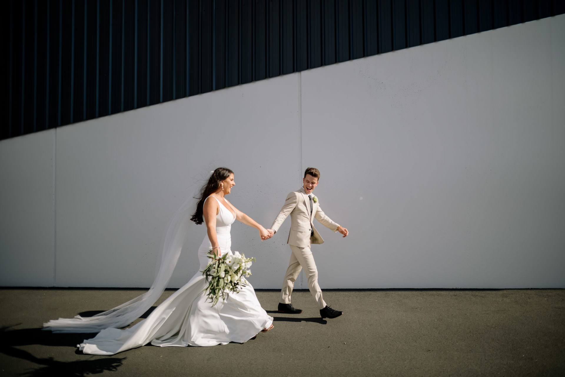 Waikato wedding photograph of bride and groom walking accross black and white wall
