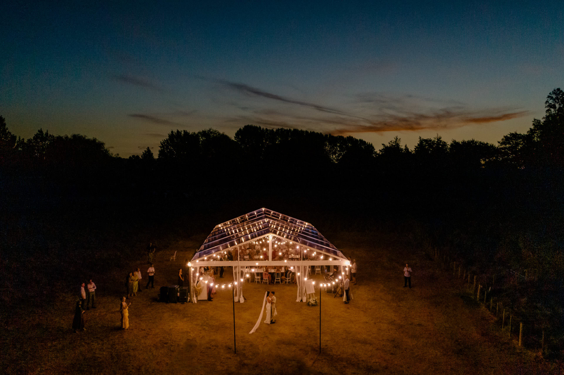 twelve tables clear marquee at night with festoons