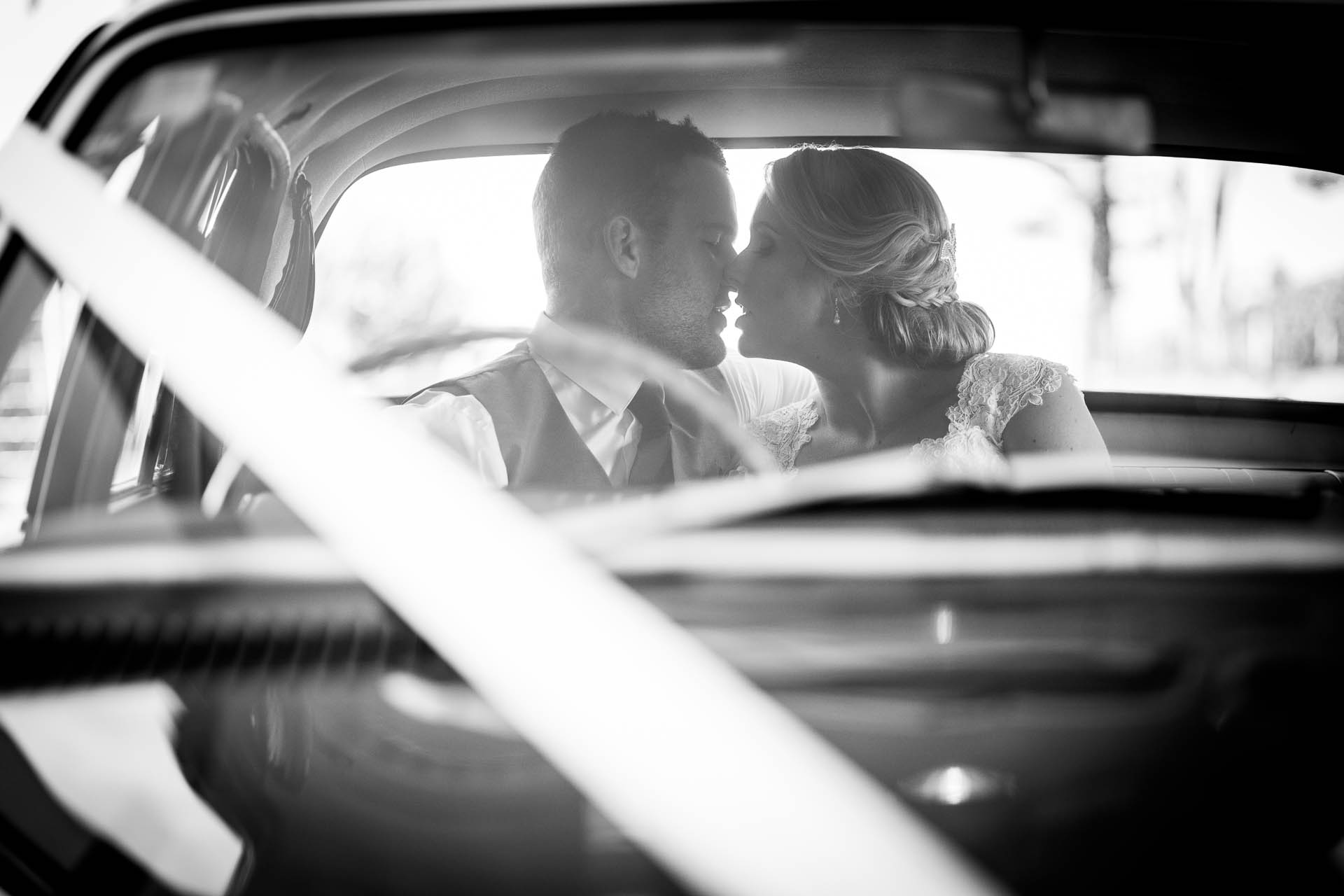 Bride-and-groom-black-white-car-kiss