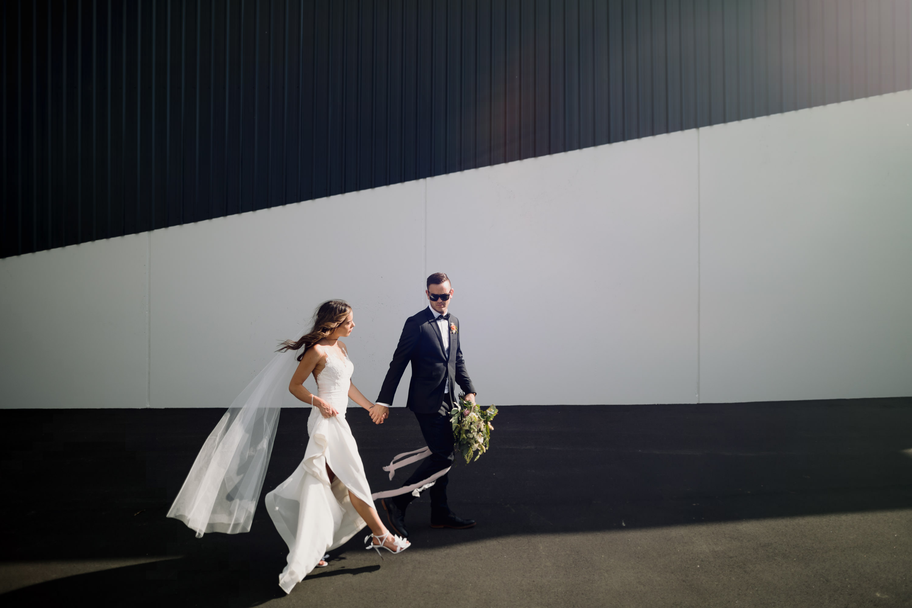 Waikato wedding photography bride and groom on black white wall